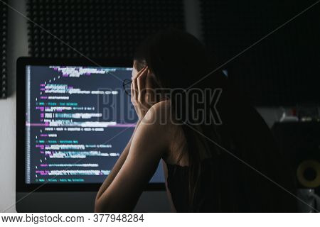 Young Caucasian Female Programmer In Glasses Writes Program Code On A Computer. Home Office. High Qu