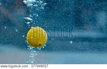 Yellow Juicy Lemon In Blue Water With Bubbles After Fall