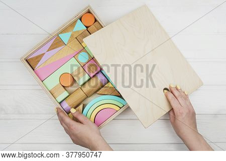 Wooden Constructor For Children. A Box Of Childrens Wooden Designer In His Hands. Colorful Toys Made