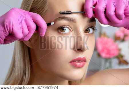 Eyelash Artist Plucks Eyebrows With Tweezers. Beautiful Blonde Woman Having Permanent Make-up Tattoo