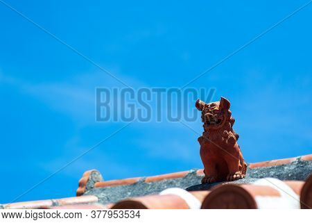 A Red Shisa Figurine Against The Red Tile Roof That Sits In The Blue Sky Of Okinawa