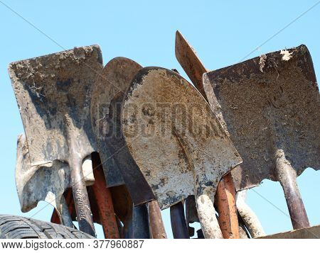 Various Types Of Shovels Used In A Landscaping Project. These Tools Were On A Rack Of A Truck Near T