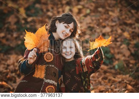Sunny Autumn Weather. Fall Concept. Fall Leaves In Girls Hands. Cheerful Smiling Woman With Sister H