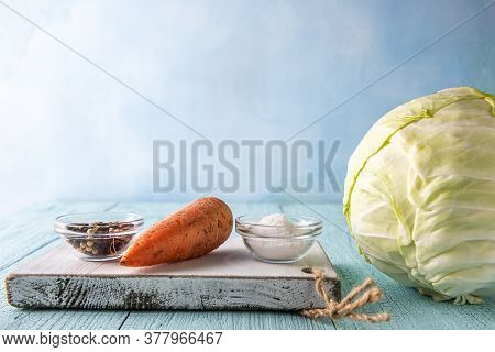 Whole Cabbage, Carrot, Assorted Pepper And White Sea Salt On Cutting Board And On Blue Wooden Table.