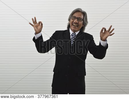 Cheerful Elderly Asian Businessman In Black Suit And Eyeglasses Showing Ok Gesture Sign With Fingers