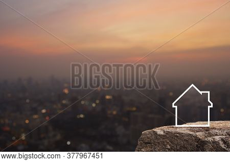 House Icon With Copy Space On Rock Mountain Over Blur Of Cityscape On Warm Light Sundown, Business R
