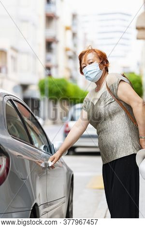Close Up Of A Mature Asian Woman Wearing A Surgical Mask Looking At The Camera On An Out Of Focus Ba