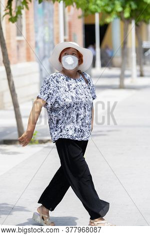 Asian Woman Wearing A Face Mask And A Hat Walking On The Streets While Looking Upwards. Traveling Co