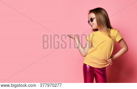 Smiling 6-7 Y.o. Kid Girl In Yellow T-shirt, Glossy Legging And Sunglasses Holds And Looks At Her Ha