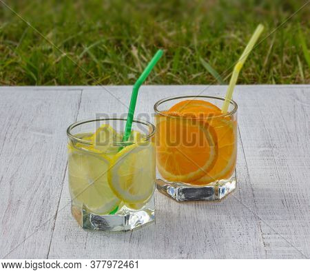 Glasses With A Refreshing Drink With Slices Of Lemons And Oranges