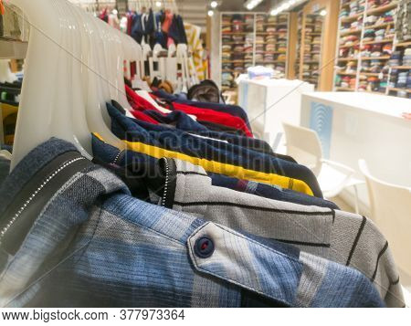 Right Side View Of An Array Of Shirts Hanging In Hangers In A Textile Showroom.the Hangers Are Hangi