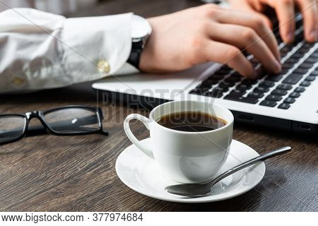 Businessman Sitting At Desk And Working With Laptop Computer. Close-up Of Man Hands Typing On Keyboa