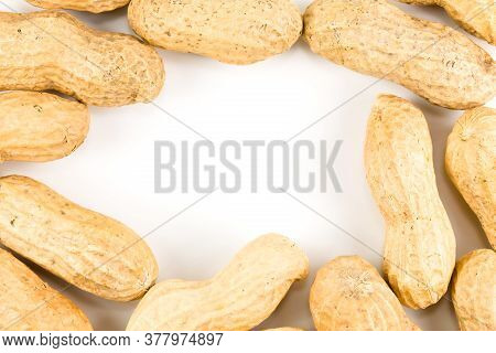 Some Dried And Closed Peanuts Isolated On White Background With Copy Space On The Left