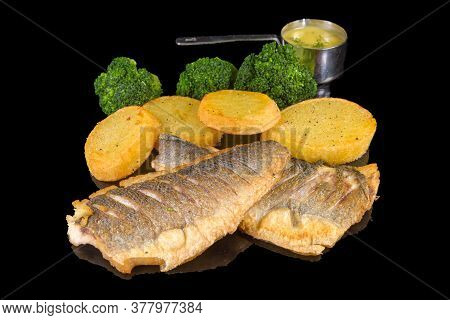 Delicious Fillet Of Sea Bass With Baked Potatoes And Broccoli With Reflection, Isolated On Black Bac