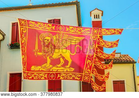 Close-up Of San Marco Flag, Saint Marco, In Italy Waving On Urban Background With Italian Style Arch