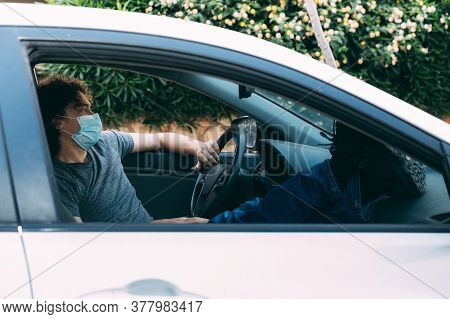 Young Curly-haired Man Sits In Car With His Legs Upstairs. Grey T-shirt And Blue Jeans. Resting Afte