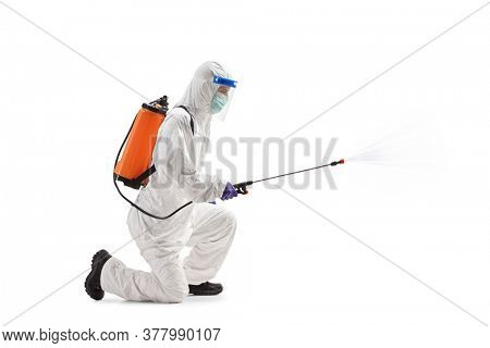 Full length profile shot of a man in a hazmat suit kneeling and using a sanitizing spray isolated on white background