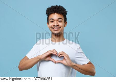 Smiling Young African American Guy In Casual White T-shirt Posing Isolated On Blue Background Studio
