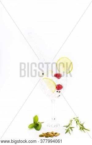 Gin And Tonic In A Goblet With Lemon, Raspberries And Black Pepper. Concept Celebration, Party. Whit