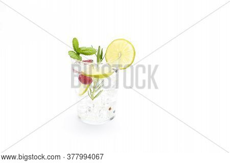 Gin And Tonic In A Glass With Lime, Mint, Rosemary And Raspberries. Concept Celebration, Party. Whit