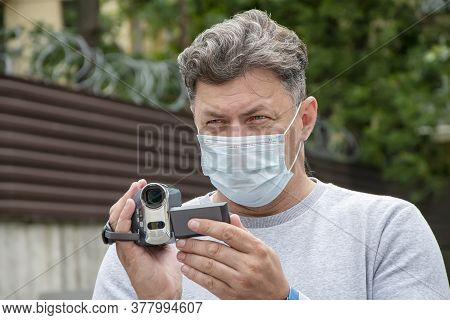 A Man In A Medical Mask Takes A Video On A Hidden Video Camera On The Street. Concept: Surveillance