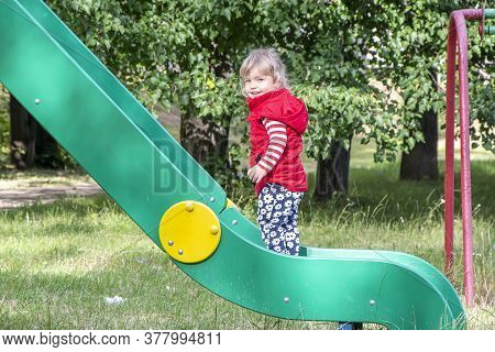 A Little Girl Slides Down A Slide On An Outdoor Playground In Summer.