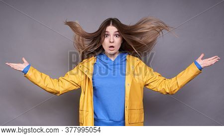 The Young Charming Surprised Caucasian Model, In A Blue Sweatshirt And Yellow Raincoat, Surprised He