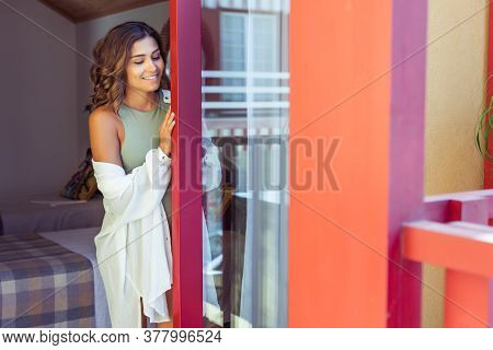 Latin Young Woman Enjoying The Sun Through The Window