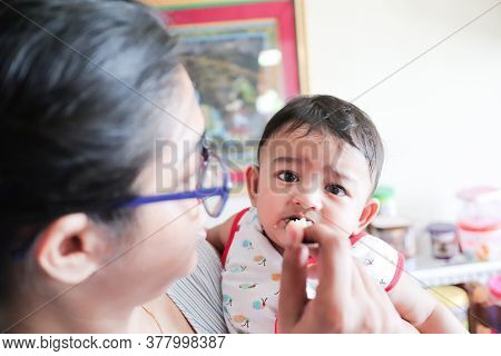 An Infant Toddler Baby Bonot Enjoying While Feeding Solid Food