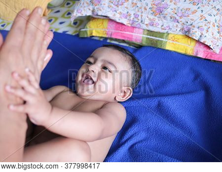 An Infant Toddler Baby Boy Smiling On A Blue Towel