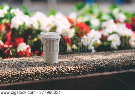 White Paper Cup With Coffee On The Street On A Background Of Blurry Colors. Disposable Cup With Plas