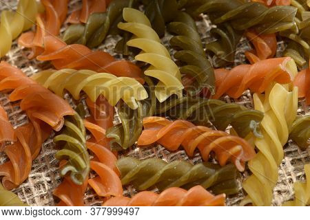 Composition Of Raw Pasta Uncooked Tricolore Fusilli, Pasta Twist Shape. Close Up And Selective Focus