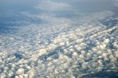 Beautiful cumulus clouds with dark blue sky just before sunset. Aerial view from plane somewhere above Shandong province China. poster