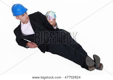 Engineer lazily lying on the floor and staring at a house made of money