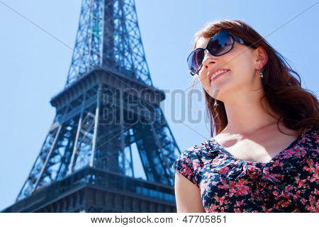 Young attractive happy woman standing and smiling against Eiffel Tower in Paris, France