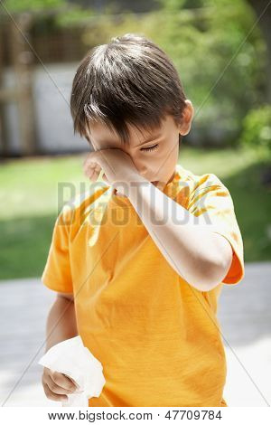 Young boy with tissue paper rubbing eye in backyard