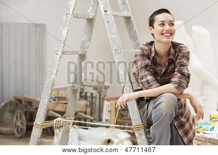 Smiling young female painter sitting on ladder at work site
