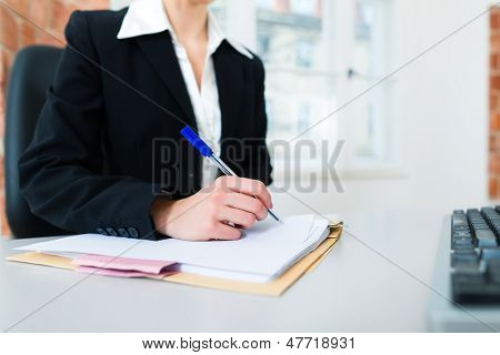 Young female lawyer or secretary working in her office and writing in a document