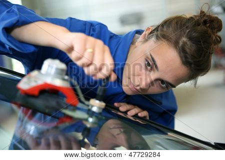 Young student in bodywork changing car windshield poster