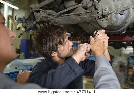 Mechanics teacher with student in car repairshop