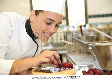 Cheerful girl at training school making cake