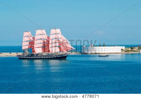 Sailing Ship With Red Sails Entering To The Bay.