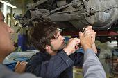 Mechanics teacher with student in car repairshop poster