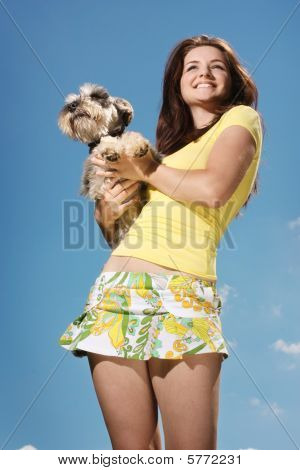 A beautiful smiling girl holding her Miniature Schnauzer on a sunny day in front of a blue sky. poster