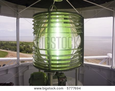 Green light is focused and concentrated through the fresnel lens atop the West Point Light in Prince Edward Island, Canada. poster