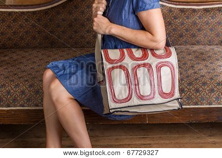Woman With Cream And Red Patterned Purse