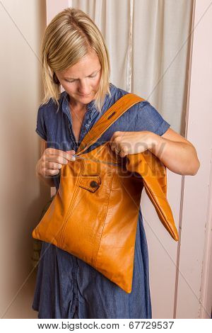 Woman In Blue Dress Looks Into A Light Brown Purse