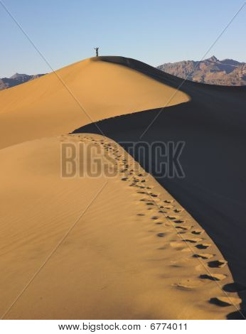 Tracks In Sand Dune With Person On Top Of Dune