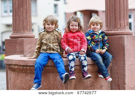 Three Siblings Sitting Together On Fountain In City