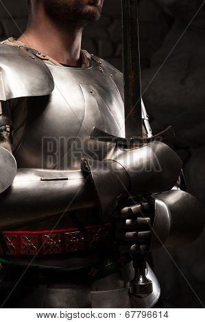 Closeup portrait of medieval knight in armor holding a sword in dark stone wall background poster